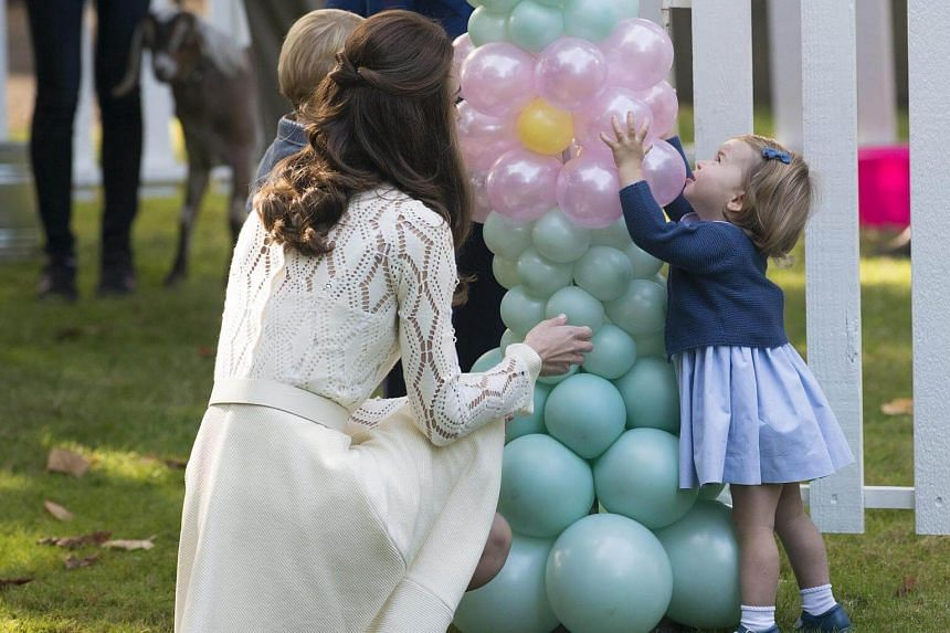 Britain's Catherine, Duchess of Cambridge (left) with Princess Charlotte (right) attend a party at the Government House in Canada.