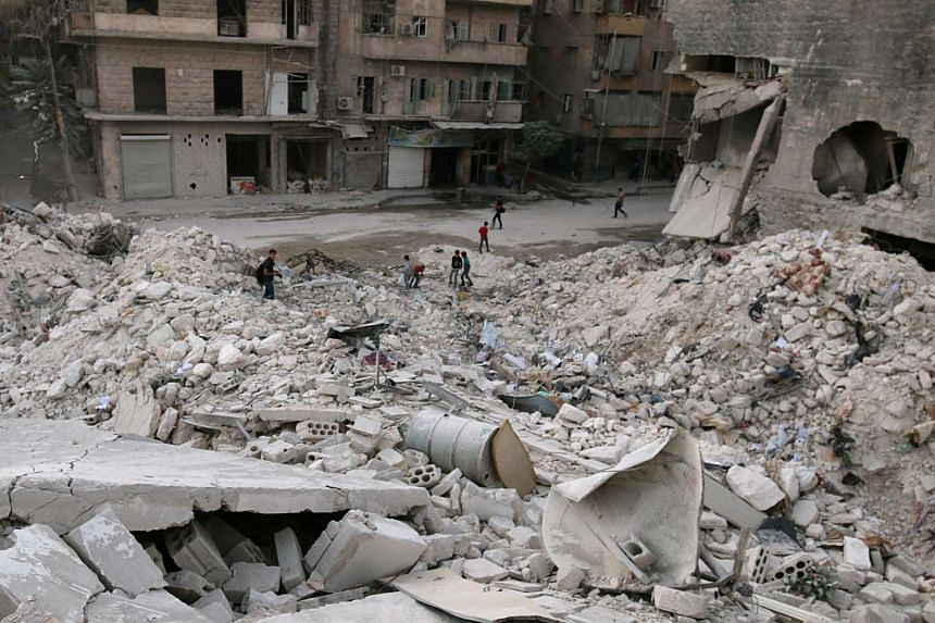 People walk on the rubble of damaged buildings in the rebel held area of al-Kalaseh neighbourhood of Aleppo, Syria on Sept 29, 2016.
