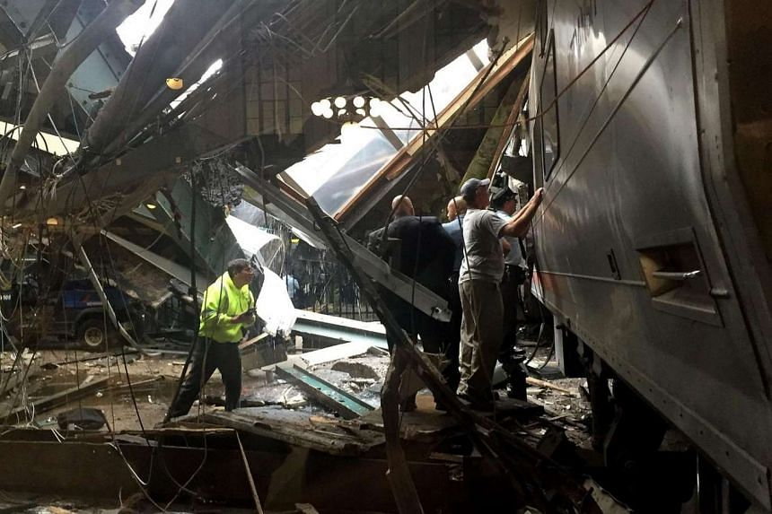 Train personnel survey the NJ Transit train that crashed into the platform at the Hoboken Terminal on Sept 29, 2016.