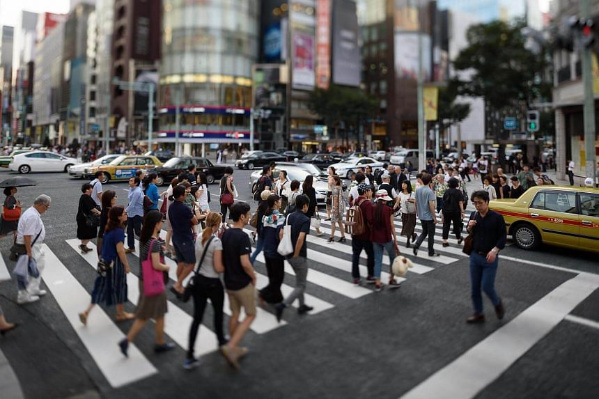 Pedestrians cross a road in the Ginza district of Tokyo, Japan, on Tuesday, Sept 27, 2016.