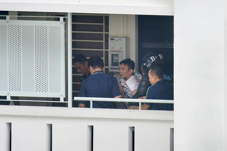 Police leading away Muhammad Iskandah Suhaimi after he locked himself in a Sembawang flat with his girlfriend's two-year-old son on Sept 28, 2016.