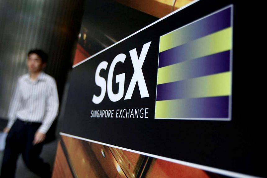 An office worker walks past a logo of the Singapore Stock Exchange (SGX) outside its premises in Singapore.