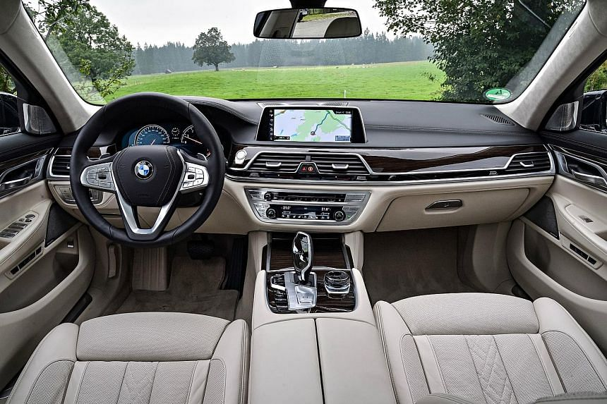 The 1983 BMW 745i (far left) features the oil change and service indicator lights on the instrument panel (top), while the 2016 BMW 750Li (left) has an intuitive cockpit (above) and is fully digitised and electrically powered.