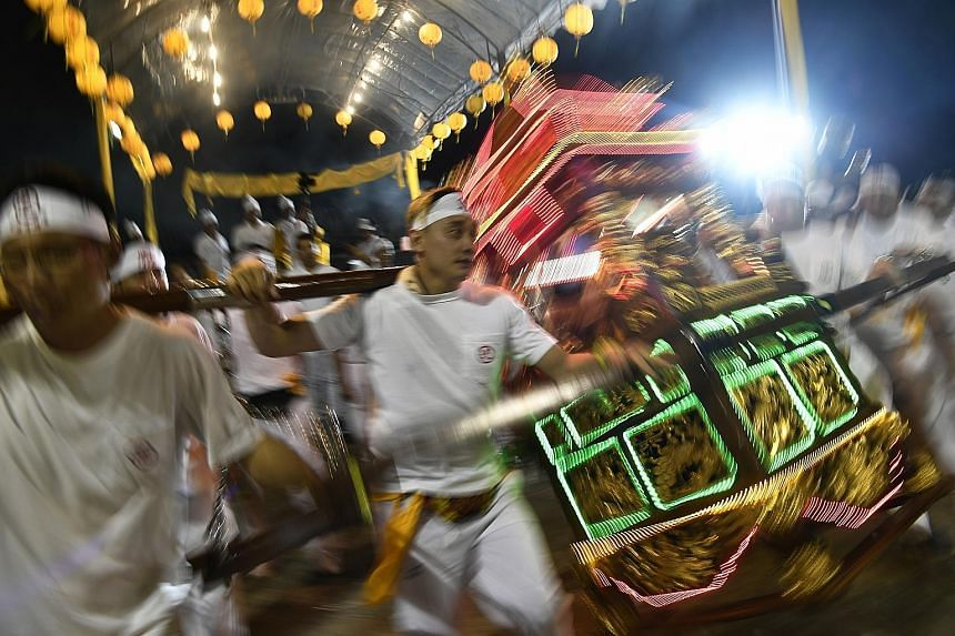 Taoist devotees last night holding a sedan chair as it sways, signifying the arrival of the Nine Emperor Gods.