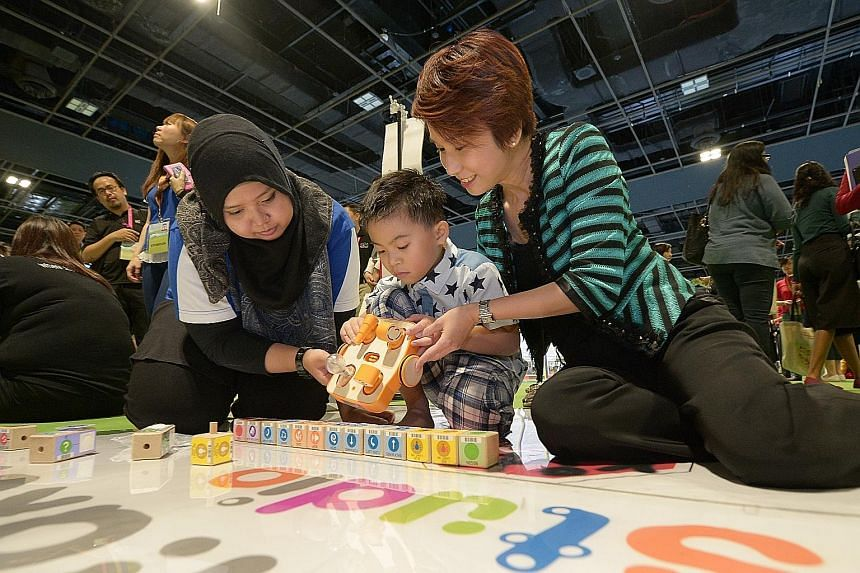 Parliamentary Secretary for Education Low Yen Ling (far right) joining six-year-old Teo Cheng Wei as he plays with Kibo, a robot programmed to move according to action commands recorded by scanning the blocks.