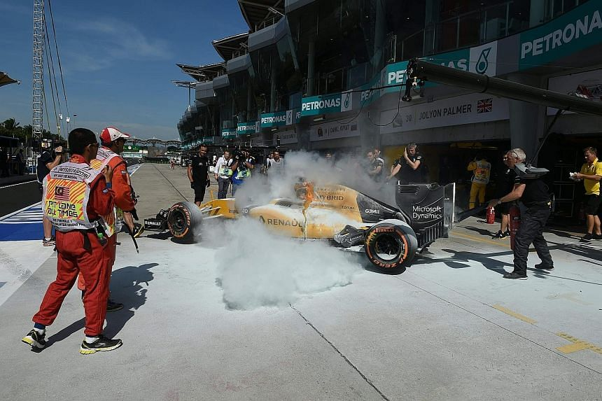 Renault driver Kevin Magnussen's car is engulfed in flames while being pushed back into the garage during first practice, forcing the Dane to make a hasty escape. The incident caused a 15-minute delay.