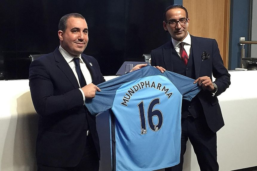 Manchester City chief operating officer Omar Berrada gives a commemorative jersey to Mundipharma's president for Asia-Pacific, Latin America, the Middle East and Africa Raman Singh (right). City and Mundipharma inked a three-year partnership on Thurs