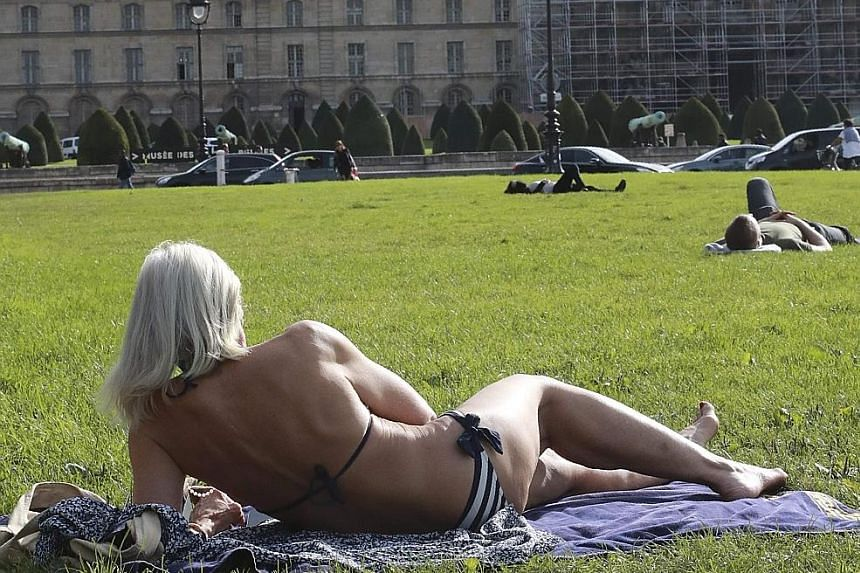 Sunbathers taking advantage of the fine weather in Paris this week. The planet has already heated up 1 deg C above the pre-industrial benchmark, scientists reported last week.