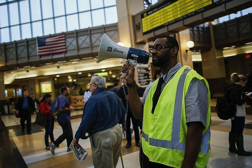 An NJ Transit worker redirecting commuters after the train crash at the Hoboken terminal on Thursday. The collision toppled support columns and created chaos.