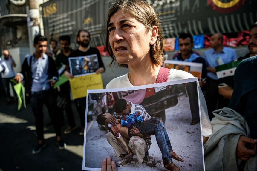 A woman holds a photo of a man mourning over the body of a boy during a protest in Istanbul on Oct 1, 2016, by Turkish activists and Syrians against the latest bombardment of Aleppo.