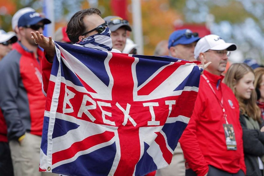 A golf fan holds a Brexit flag during practice for the 2016 Ryder Cup in the US on Sept 29, 2016.