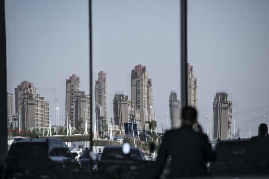 A pedestrian on a mobile handset walks past a glass window as traffic and residential buildings are reflected in Tianjin, China.