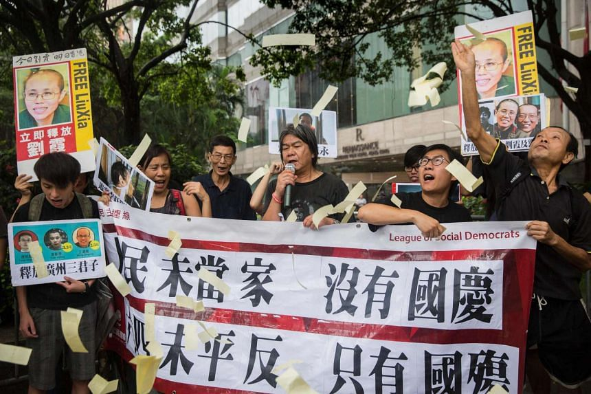Protesters from the League of Social Democrats, throw hell money during a protest on China's National Day in Hong Kong.