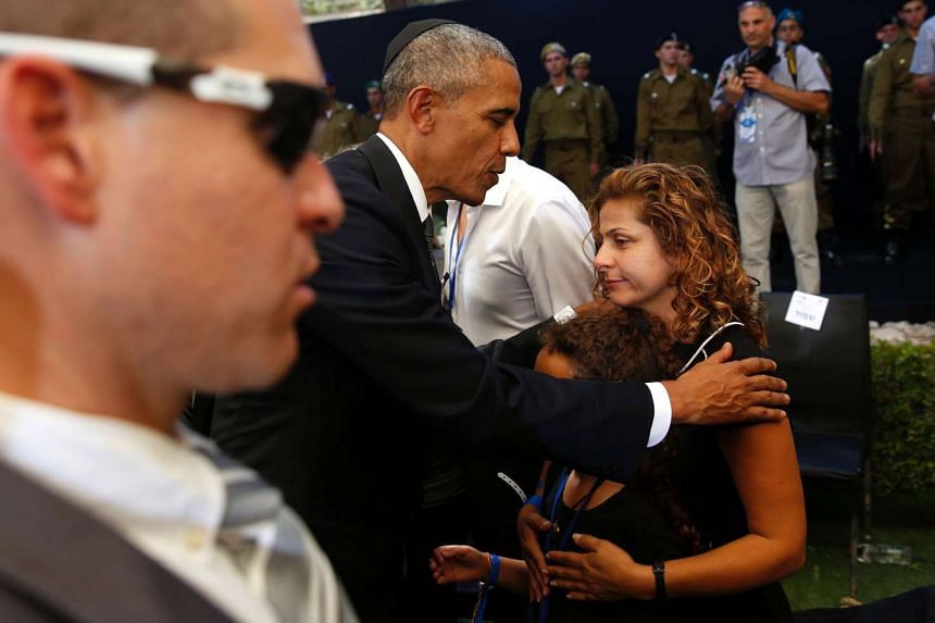 US President Barack Obama consoles family members, after the burial ceremony.