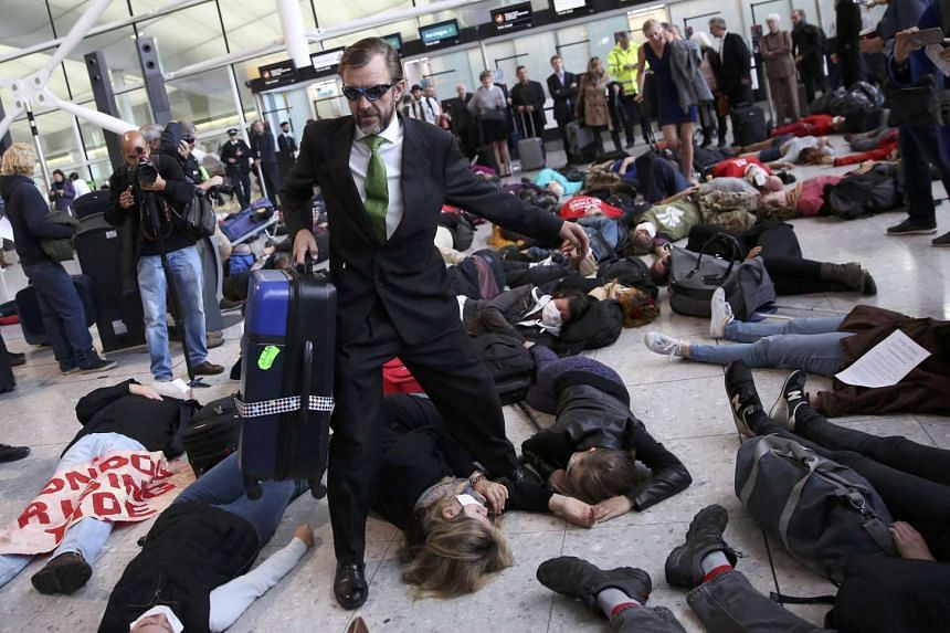 Protesters lay on the floor of Heathrow's Terminal 2, to highlight the impact of air travel on climate change and pollution levels.