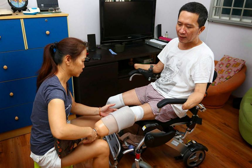 Mr Tan Whee Boon (right) with his wife, Madam Choong Siet Mei putting on his prosthetic limbs.
