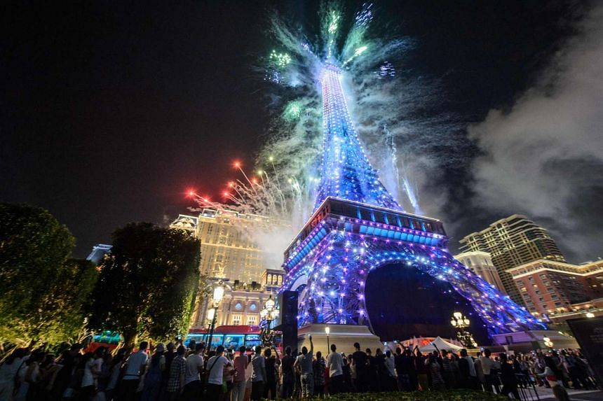 People gather to watch fireworks exploding from a replica of the Eiffel Tower after the opening of the Sands new mega resort The Parisian in Macau, on Sept 13, 2016.