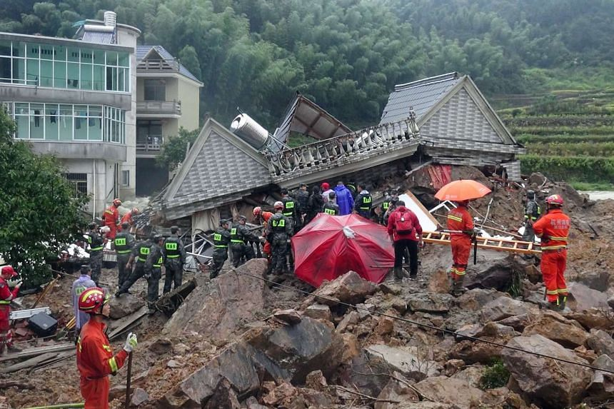Chinese rescuers search for survivors at a landslide area in the village of Sucun in Suichang county on Sept 29, 2016.