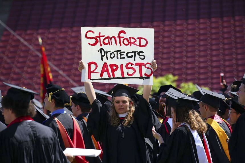 A protester holds a sign during graduation exercises at Stanford University on June 12, 2016.