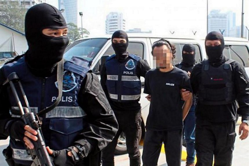 A man believed to be member of the Islamic State in Iraq and Syria (ISIS) being detained by the Malaysian police.
