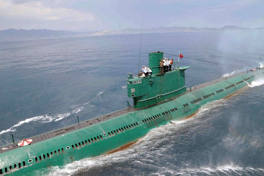 North Korean leader Kim Jong Un (left) stands on the conning tower of a submarine during his inspection of the Korean People's Army (KPA) Naval Unit.