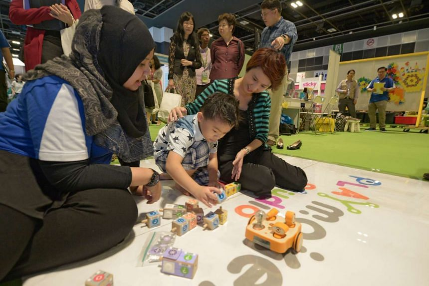 Parliamentary Secretary, Ministry of Education and Ministry of Trade and Industry, Ms Low Yen Ling and six-year-old Teo Cheng Wei (centre), playing Kibo, a robot programmed to move according to action commands during the Early Childhood Conference 20