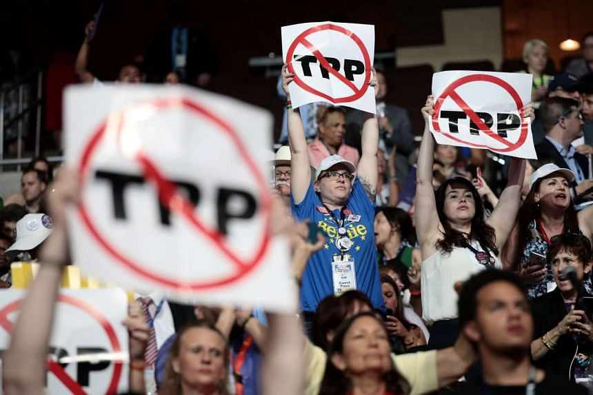 Delegates against the Trans-Pacific Partnership (TPP) hold up signs on the first day of the Democratic National Convention at the Wells Fargo Centre.