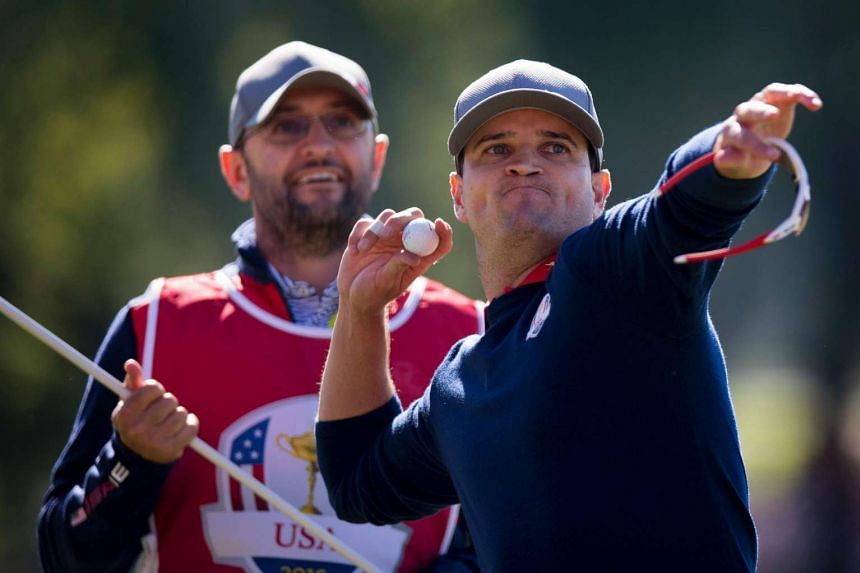 The US'  Zach Johnson throws his ball as he celebrates his win during the Morning Foursome matches.