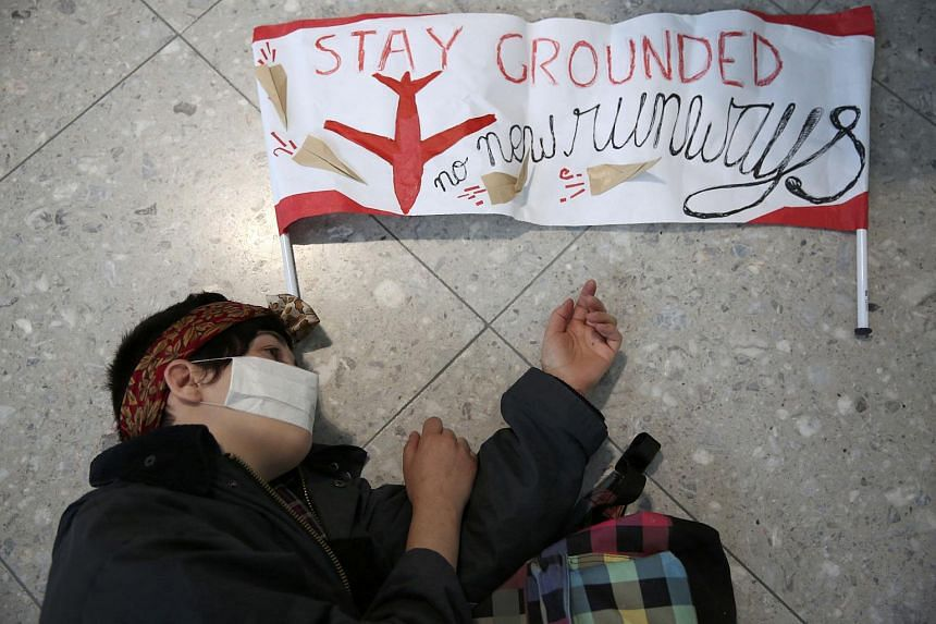 A climate activist from the group Reclaim the Power lies on the ground during a protest against airport expansion plans at Heathrow Airport in London on Oct 1, 2016.