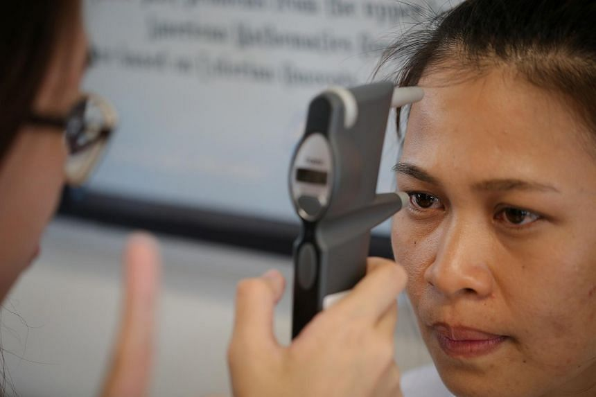 Ledy Jilly Bongolo, 28, a foreign domestic worker from Indonesia, has her eye pressure measured using a tonometer.