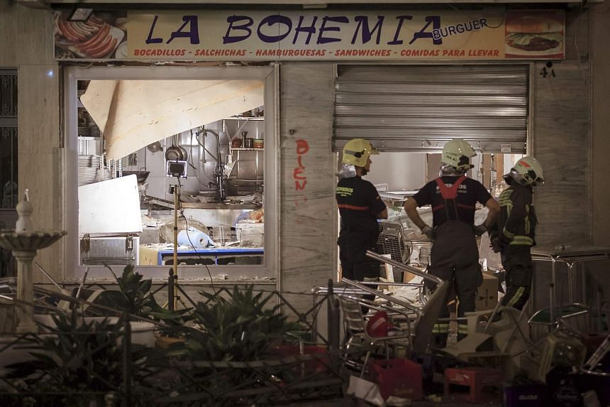 Firefighters standing at the entrance of the restaurant where a gas cylinder exploded in Malaga, southern Spain, on Oct 1, 2016.