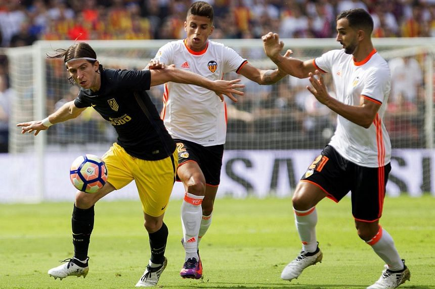 Valencia's Joao Cancelo (centre) and Martin Montoya fight for the ball with Atletico Madrid's Filipe Luis (left) during their Spanish Primera Division soccer match on Oct 2, 2016.