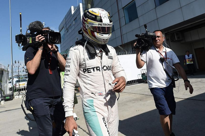 Mercedes AMG Petronas F1 Team's British driver Lewis Hamilton arrives the pit, after his car engine caught fire during the Formula One Malaysian Grand Prix in Sepang on Oct 2, 2016.
