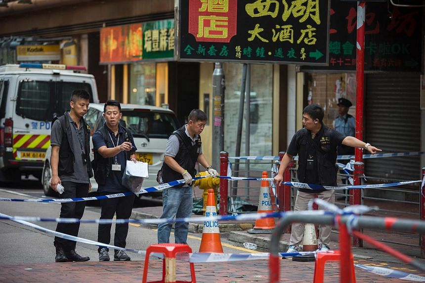 Forensic investigators looking for evidence at a crime scene where police officers opened fire on a gang of men fighting in the Yau Ma Tei district of Hong Kong on Oct 2, 2016.