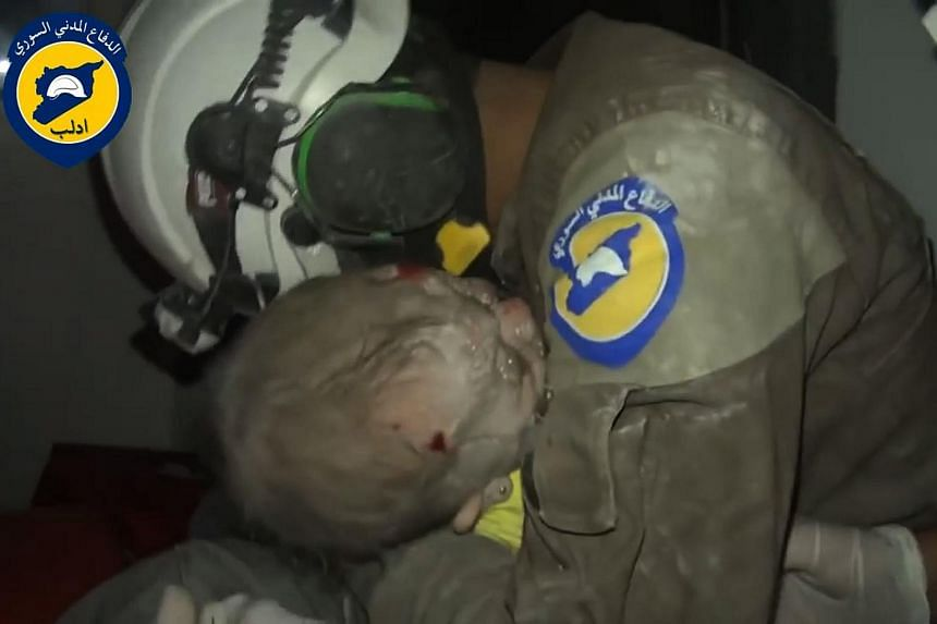 A Syrian civil defence member from the White Helmets cries after rescuing four-month-old Wahida from the rubble of her home, in  Idlib on Sept 29, 2016.