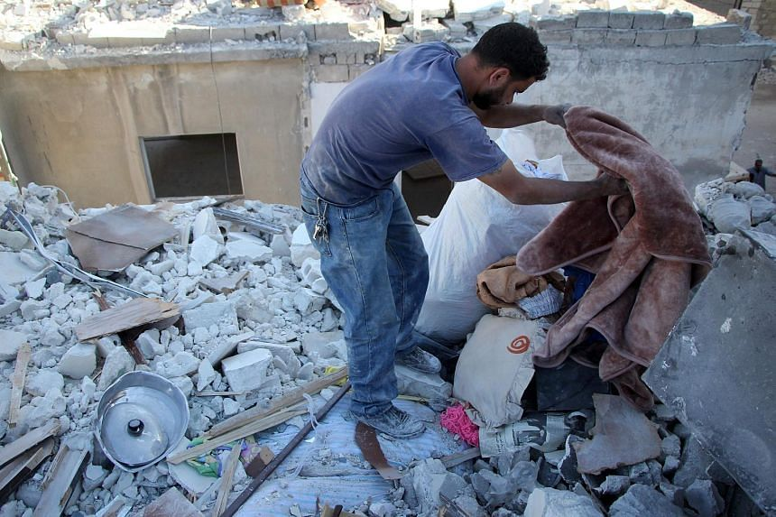 Syrian Yehya Maatouq, the father of four-month-old Wahida, searching for the family's belongings in the rubble of their home on Oct 1, 2016.