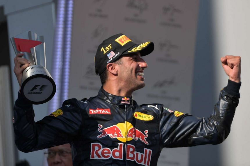 Red Bull Racing's Daniel Ricciardo holds the trophy as he celebrates taking first place at the Formula One Malaysian Grand Prix in Sepang on Oct 2, 2016.