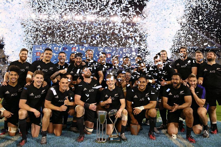 The New Zealand All Blacks celebrate with the Rugby Championship trophy after their win against Argentina.