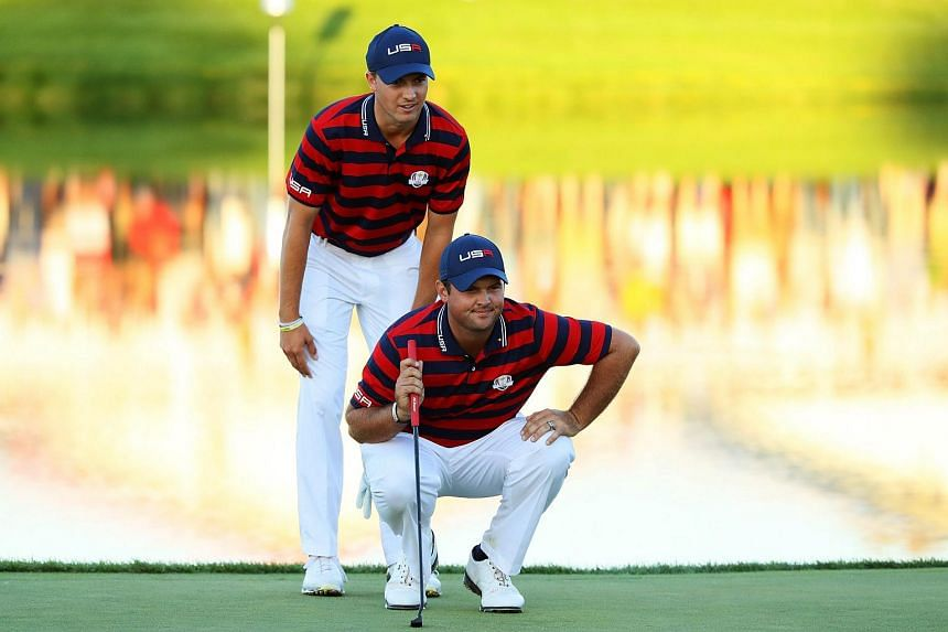 Jordan Spieth and Patrick Reed of the United States line up a putt on the 17th green during afternoon fourball matches of the 2016 Ryder Cup at Hazeltine National Golf Club on Oct 1, 2016.