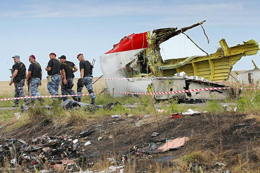 A file photo from 2014 showing armed rebel soldiers passing a big piece of debris at the main crash site of the Boeing 777 Malaysia Airlines flight MH17.