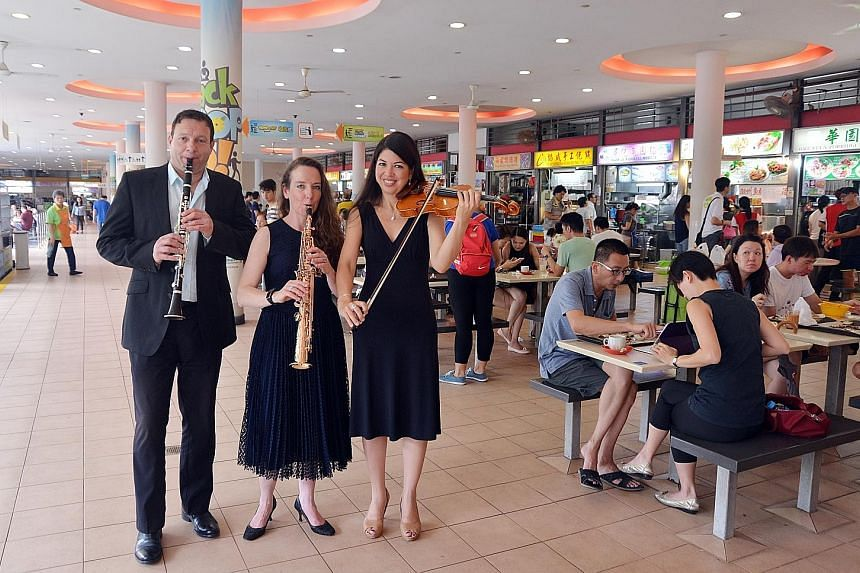 Visitors to Tiong Bahru market yesterday were greeted by an unusual sight - members of the Australian World Orchestra going around taking photographs with curious residents. Among the musicians were (from left) clarinetist Frank Celata, saxophonist C