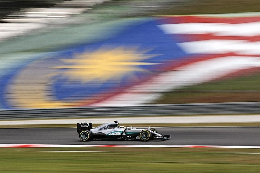 Lewis Hamilton of Mercedes steering his car past a Malaysian flag during the qualifying session for the Malaysian Grand Prix in Sepang yesterday. He starts in pole position for today's race, ahead of team-mate and title rival Nico Rosberg.