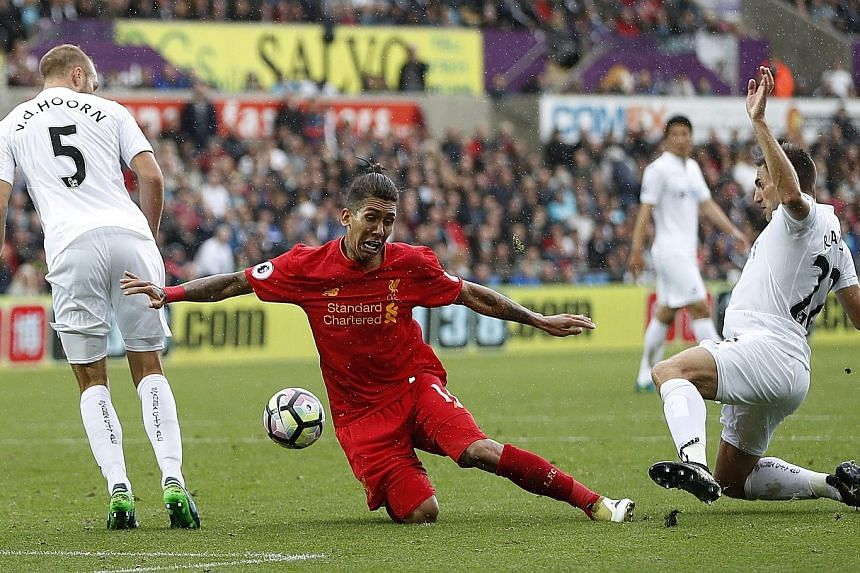 Liverpool's Roberto Firmino is fouled by Swansea's Angel Rangel, resulting in a penalty which James Milner tucked away late on. The Brazilian had headed the Reds level earlier, as they recovered from a horrid first half.