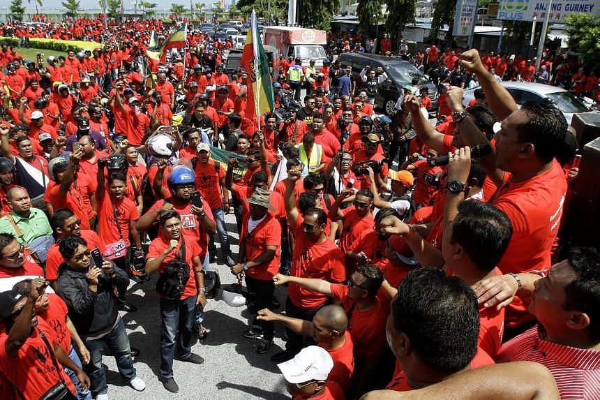 Bersih members (left) drumming up support for their movement in Gelang Patah, Johor yesterday while an anti-Bersih group dressed in red shirts (above) hold their own demonstration in Penang.