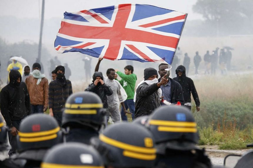 """Tear gas fills the air as French riot police face off with demonstrators near the area called the """"Jungle"""" where migrants live in Calais, France, Oct 1, 2016."""