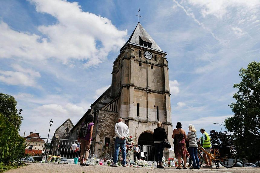 People gathering in front of the church of Saint-Etienne-du-Rouvray in northern France on July 28, 2016, where French priest Jacques Hamel was killed.