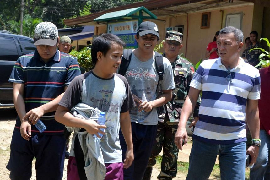 Soldiers and local government officials escorting three Indonesian hostages at an army camp after they were released by Abu Sayyaf rebels in Jolo, Sulu province, on Oct 2, 2016.