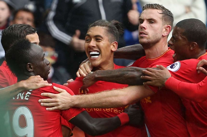Liverpool's Brazilian midfielder Roberto Firmino (centre) celebrates scoring their first goal to equalise 1-1 against Swansea City.