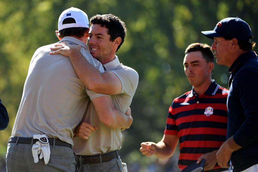 Thomas Pieters and Rory McIlroy react after winning their match on the 16th green with Rickie Fowler and Phil Mickelson of the US during morning foursome matches.