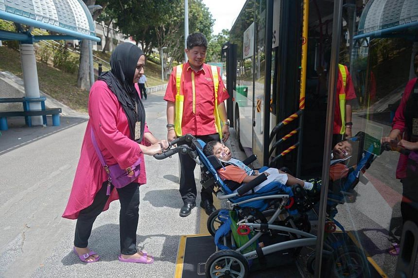 Madam Mutmainnabibi Angullia boarding the bus with her son Ashad Singh, who suffers from cerebral palsy.